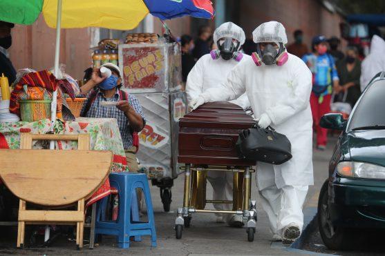 Quienes ingieren alimentos afuera del hospital San Juan de Dios pueden observar a los empleados de las funerarias pasar con los difuntos. Foto Prensa Libre: Érick Ávila