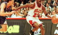 """(FILES) In this file photo taken on June 4, 1997 Chicago Bulls player Michael Jordan sticks out his tongue as he goes past Jeff Hornacek of the Utah Jazz during game two of the NBA Finals at the United Center in Chicago, IL. - The immense global success of the documentary """"The Last Dance"""" amid the coronavirus lockdown has boosted sales of collectibles related to NBA icon Michael Jordan, some of which are trading in the hundreds of thousands of dollars. (Photo by VINCENT LAFORET / AFP)"""