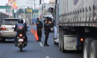 Agentes de la Policía Nacional Civil verifican documentación de constransporte de carga. (Foto Prensa Libre, Juan Diego González)