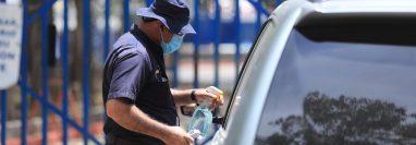 Un agente de seguridad toma la temperatura en la entrada de un Hospital público. Foto Prensa Libre: Juan Diego González