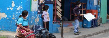 Ante la mirada de su madre, un niño con una bandera blanca en Quiché, pide víveres o dinero por la crisis de la pandemia. (Foto Prensa Libre: Héctor Cordero)