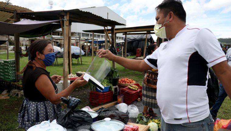 Eleazar Arango entrega protectores faciales a comerciantes en distintos mercados de Huehuetenango. (Foto Prensa Libre: Mike Castillo)