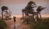 TOPSHOT - COCOA BEACH, FLORIDA - SEPTEMBER 02: A woman takes a picture as the effects of Hurricane Dorian begin to be felt on September 2, 2019 in Cocoa Beach, Florida. Dorian, once expected to make landfall near Cocoa Beach as a category 4 storm, is currently predicted to turn north and stay off the Florida coast, lessening the impact on the area.   Scott Olson/Getty Images/AFP (Photo by SCOTT OLSON / GETTY IMAGES NORTH AMERICA / AFP)