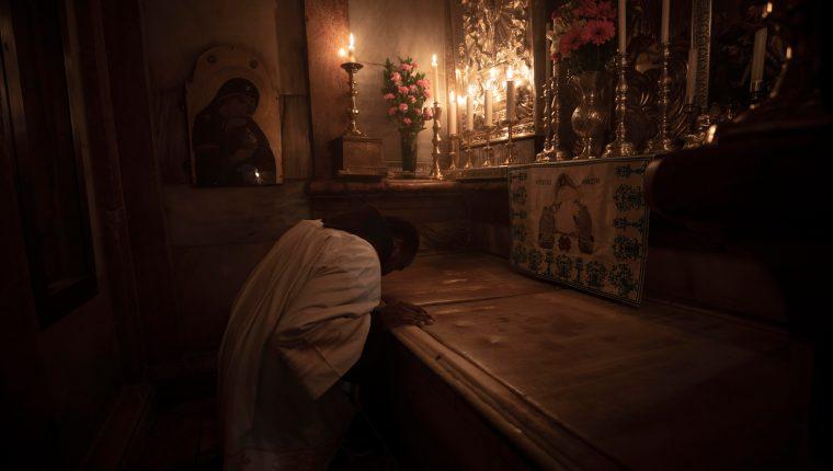 Un monje franciscano reza en la losa de mármol que cubre la Tumba de Jesús, en la Basílica del Santo Sepulcro, que abre sus puertas al público este domingo. (Foto Prensa Libre: EFE)