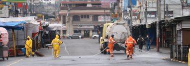 Trabajadores municipales desinfectan áreas del mercado La Democracia donde se afirmó un caso positivo de covid-19. (Foto Prensa Libre: Raúl Juárez)