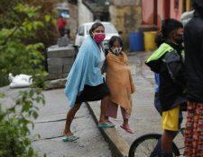 Miembros de una familia fueron evacuados a causa de un deslave en el anexo 2, colonia El Rosario, zona 18, este domingo. (Foto Prensa Libre: Esbin García).