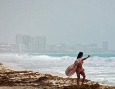 Algunas personas aprovechan la llegada del fenómeno para tomarse fotos en Cancún, México. AFP