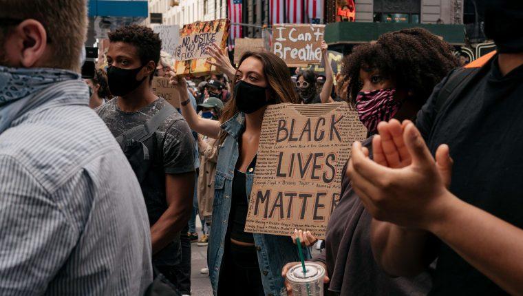 Manifestantes levantan carteles y cantan durante una manifestación en el Times Square denunciando el racismo en la aplicación de la ley y el asesinato de George Floyd, el 1 de junio de 2020. (Foto Prensa Libre: AFP).