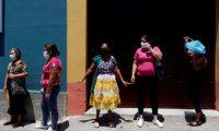 AME9803. CIUDAD DE GUATEMALA (GUATEMALA), 02/04/2020.- Viudas de pilotos asesinados en Guatemala esperan para recibir bolsas con comida entregada por el Ministerio de Desarrollo Social como ayuda durante las restricciones comerciales y de movilidad para prevenir el contagio del coronavirus, en Ciudad de Guatemala (Guatemala). Guatemala sumó este jueves un caso más al listado de contagios por SARS-CoV-2, por lo que alcanzó los 47 contagios, entre quienes se cuenta un fallecido, tres personas graves en el intensivo y 12 recuperados. El país centroamericano tiene a más de 2.800 personas en cuarentena obligatoria y otras 1.200 ya fueron liberadas de la medida restrictiva al no haber presentado síntomas, de acuerdo a datos del ministerio de Salud. EFE/Esteban Biba