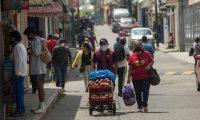 GU5001. SAN LUCAS (GUATEMALA), 15/05/2020.- Un grupo de personas se aprovisiona de alimentos antes del horario de prohibición bajo la vigilancia de la Policía municipal, que inspecciona que los negocios cierren a las 11 de la mañana en punto en San Lucas, Sacatepéquez. Los guatemaltecos solo tienen 3 horas al día para proveerse en tiendas locales de alimentos y solo se pueden desplazarse a pie según las nuevas dispociciones del presidente Alejandro Giammattei. El presidente de Guatemala, Alejandro Giammattei, ordenó nuevas medidas de confinamiento tras informar a la población sobre 176 nuevos contagios de coronavirus, la cifra diaria más alta desde que se detectó el primer caso el 13 de marzo. EFE/Esteban Biba