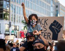 Un hombre y un niño participan en las protestas por la muerte de George Floyd cerca de la Casa Blanca. Foto Prensa Libre