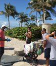 Unos jóvenes revisan las máscaras de unas personas a su llegada a la playa de Miami Beach, Florida, el 10 de junio de 2020. (Foto Prensa Libre: EFE).