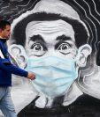 """Un hombre pasa este jueves frente a un grafitti del actor mexicano Ramón Valdés y su personaje """"Don Ramón"""" con tapabocas, en Montevideo, Uruguay. (Foto Prensa Libre: EFE)"""