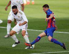 El defensa del Real Madrid Dani Carvajal, quien se resintió de un golpe (i), pelea un balón con el centrocampista uruguayo del Eibar.  (Foto Prensa Libre: EFE)
