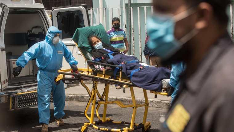 Paramédicos trasladan a un mujer con síntomas de coronavirus al hospital general San Juan de Dios. (Foto Prensa Libre: EFE)