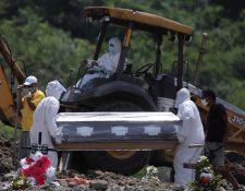 Un grupo de personas participa en un entierro en el cementerio Jardín de Paz Los Ángeles, destinado para entierros de personas que fallecen por el coronavirus en Tegucigalpa. (Foto Prensa Libre: EFE)