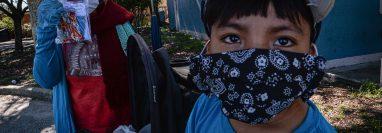 Una agricultora y su nieto visten tapabocas para protegerse del contagio covid-19 en una finca de Immokalee, Florida, donde trabajan miles de migrantes guatemaltecos. (Foto Prensa Libre: EFE)