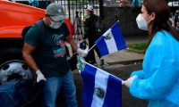 A health worker gives a Salvadoran flag to a citizen upon his arrival to a center where he and others will be quarantined to prevent the spread of the new coronavirus after being repatriated from Honduras, in San Salvador on May 1, 2020. - The Salvadoran Ministry of Foreign Affairs started a repatriation program for citizens who, due to the COVID-19 pandemic were stranded in different countries. (Photo by Yuri CORTEZ / AFP)