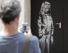 En esta foto de archivo tomada el 25 de junio de 2018, un hombre toma una fotografía de una obra de arte del artista callejero Banksy en París en una calle lateral a la sala de conciertos Bataclan donde un ataque terrorista mató a 90 personas el 13 de noviembre de 2015. (Foto Prensa Libre: AFP).