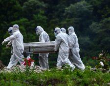 Varios hombres con trajes protectores llevan el cuerpo de una víctima de covid-19. (Foto Prensa Libre: AFP)