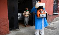 A woman speaks to a police officer wearing a protective suit after he disinfected the coffin of a 73-year-old suspected COVID-19 victim, in Guatemala City on June 29, 2020 amid the novel coronavirus pandemic. - Guatemala is approaching the 17,000 COVID-19 infections, while 727 people have died so far in the country. (Photo by Johan ORDONEZ / AFP)