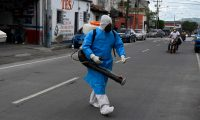 A police officer wearing a protective suit arrives to disinfect the coffin of a 73-year-old suspected COVID-19 victim, in Guatemala City on June 29, 2020 amid the novel coronavirus pandemic. - Guatemala is approaching the 17,000 COVID-19 infections, while 727 people have died so far in the country. (Photo by Johan ORDONEZ / AFP)
