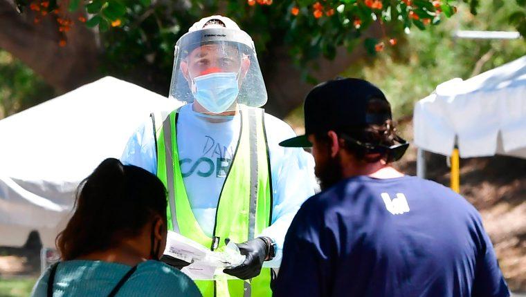 Un voluntario vestido con protección completa ofrece kits de prueba a las personas en un sitio de prueba covid-19 sin cita previa, en Los Ángeles, California. (Foto Prensa Libre: AFP)