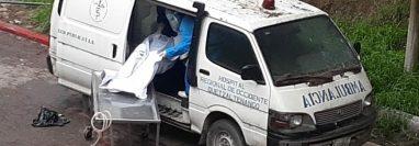 Empleados del Hospital Regional de Occidente ingresan el cadáver de una víctima de covid-19 a una vieja ambulancia que sirve como morgue. (Foto Prensa Libre: Raúl Juárez)