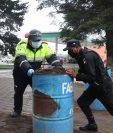 Policía Municipal de Tránsito y PNC liberan los ingresos donde se instalaron toneles. (Foto Prensa Libre: Raúl Juárez)