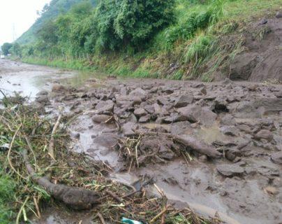 Deslizamiento arrastró piedras, vegetación y lodo sobre el asfalto. (Foto Prensa Libre: PMT Villa Nueva)