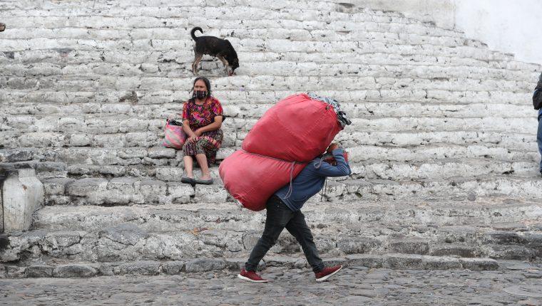 Minutos antes del toque de queda, un comerciante se apresura a guardar su mercadería, mientras una dama espera en las gradas de la iglesia. Foto Prensa Libre: Érick Ávila)