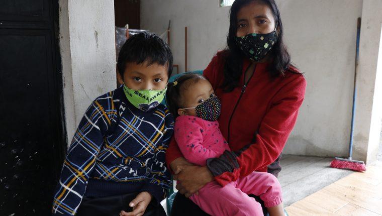 Gloria Noemí Cojolón y sus dos hijos, Dulce Abigail y Javier Alexánder, recuerda a su esposo, Antonio Castillo, desaparecido durante la erupción del Volcán de Fuego de hace dos años. (Foto Prensa Libre: Julio Sicán)