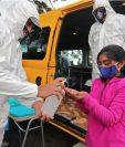 Una niña recibe alcohol en gel para recibir clases en la furgoneta. (Foto Prensa Libre: AFP)