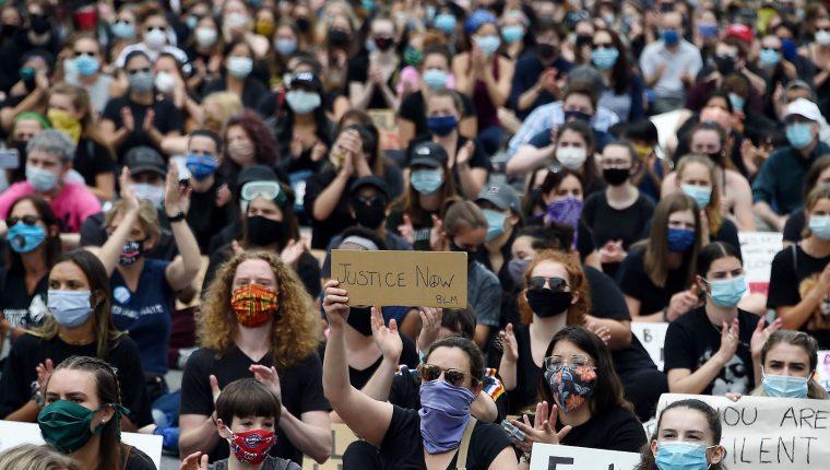 Manifestantes sostienen carteles mientras protestan en EE. UU. por la muerte de George Floyd. (Foto Prensa Libre: AFP)