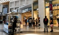 """Customers stand in line outside """"Forever 21"""" store inside a Mall west of Fort Lauderdale, Florida on May 18, 2020. - South Florida begins a gradual reopening of its economy on May 18,2020 with the start of activities of some restaurants and businesses in Miami and Fort Lauderdale, but the beaches will still be closed until further notice.The opening """"phase 1"""" in this region also does not include hotels, bars, nightclubs, gyms, movie theatres or massage parlours. (Photo by CHANDAN KHANNA / AFP)"""
