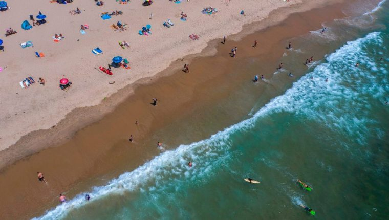 Expertos dicen que la reapertura del comercio y playas en California aceleraron los contagios. (Foto Prensa Libre: AFP)