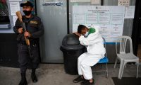 A penitentiary system guard scorts an inmate with symptoms related to the novel coronavirus at the COVID-19 unit of San Juan de Dios hospital in Guatemala City on July 13, 2020. (Photo by Johan ORDONEZ / AFP)