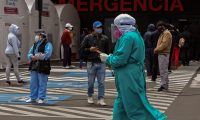 A health worker walks past people keeping safety distance outside a tent for respiratory triage and care for patients with a COVID-19 symptoms, outside the emergency room of the IESS Sur Hospital, in Quito, on July 20, 2020. (Photo by Cristina Vega RHOR / AFP)