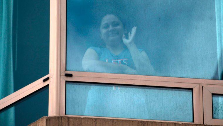 Desde la ventana de la habitación donde se recupera de coronavirus, Yoselin Solórzano saluda a su novio, Miguel Ángel Taque. (Foto Prensa Libre: AFP)