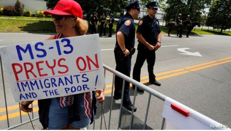 Archivo - Una simpatizante del presidente de Estados Unidos, Donald Trump, sostiene un cartel que dice que la MS-13 caza a inmigrantes y pobres. (Foto Prensa Libre: La Voz de América)
