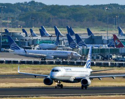Un avión de Copa Airlines es visto en una pista mientras otro aterriza del aeropuerto internacional de Tocumen, el 22 de marzo de 2020.  (Foto Prensa Libre: La Voz de América)