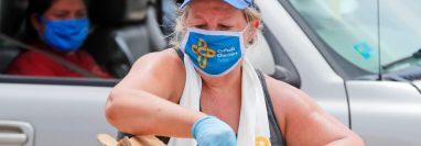 Usando una mascarilla en medio de preocupaciones por el coronavirus, la voluntaria Karen Cooperstein descarga galones de leche para donar al público durante un evento de donación de alimentos de Catholic Charities, en Dallas, Texas. (Foto Prensa Libre: VOA)