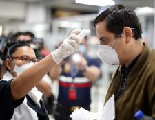 Un pasajero es revisado con un escáner térmico por un trabajador de salud pública en el aeropuerto internacional Óscar Romero y Galdamez, en El Salvador, el 12 de marzo de 2020.