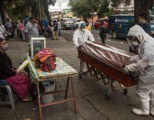Empleados funerarios trasladan el féretro de una víctima de coronavirus, quien murió en la emergencia del Hospital Nacional San Juan de Dios el 28 de mayo de 2020. (Foto Prensa Libre: EFE)