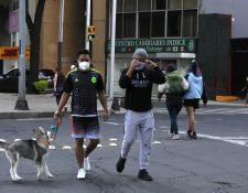 Dos hombres usan mascarilla, mientras pasean con su perro en una calle de la ciudad de México. Foto Prensa Libre: EFE