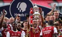 Arsenal's Gabonese striker Pierre-Emerick Aubameyang holds the winner's trophy as the team celebrates victory after the English FA Cup final football match between Arsenal and Chelsea at Wembley Stadium in London, on August 1, 2020. - Arsenal won the match 2-1. (Photo by Adam Davy / POOL / AFP) / NOT FOR MARKETING OR ADVERTISING USE / RESTRICTED TO EDITORIAL USE