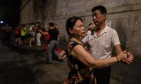 TOPSHOT - This photo taken on August 5, 2020 shows couples dancing next to the Yangtze River in Wuhan in China's central Hubei province. - The city's convalescence since a 76-day quarantine was lifted in April has brought life and gridlocked traffic back onto its streets, even as residents struggle to find their feet again. Long lines of customers now stretch outside breakfast stands, a far cry from the terrified crowds who queued at city hospitals in the first weeks after a city-wide lockdown was imposed in late January to curb the spread of the COVID-19 coronavirus. (Photo by Hector RETAMAL / AFP)