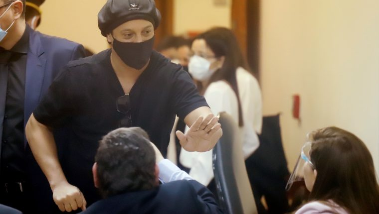 El exfutbolista brasileño Ronaldinho Gaúcho se despide de los fiscales al final de una audiencia en el Palacio de Justicia en Asunción, Paraguay. (Foto Prensa Libre: EFE)
