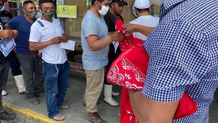 Guatemaltecos de Indiantown que laboran en fincas agrícolas hacen fila para recibir pañuelos y mascarillas para prevenir el contagio del covid-19. (Foto: Cortesía)