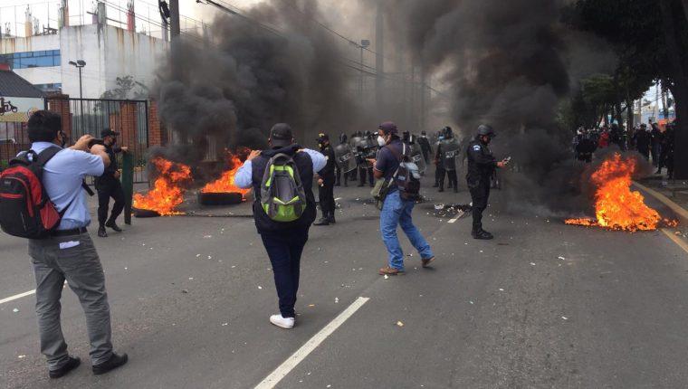 Agentes antidisturbios de la PNC retiran el bloqueo en la avenida Petapa y habilitan el paso vehicular. (Foto Prensa Libre: )